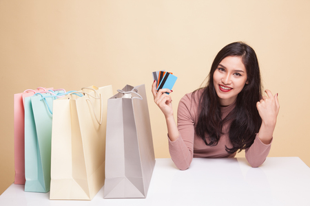 Young Asian woman happy with shopping bag on beige background 免版税图像