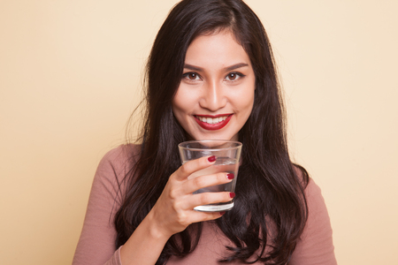Young Asian woman with tomato juice and red heart on beige background