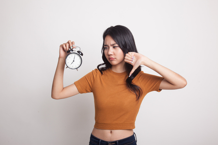 Young Asian woman thumbs down with a clock on white background