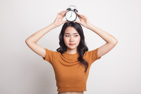 Young Asian woman smile with a clock on white background