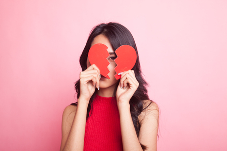 Beautiful young Asian woman with broken heart on pink background