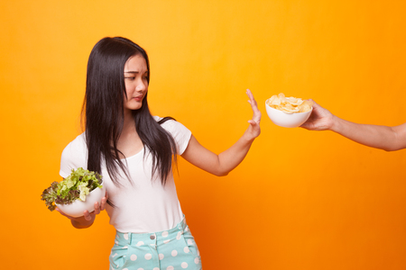 Young Asian woman with potato chips say no to salad on bright yellow background