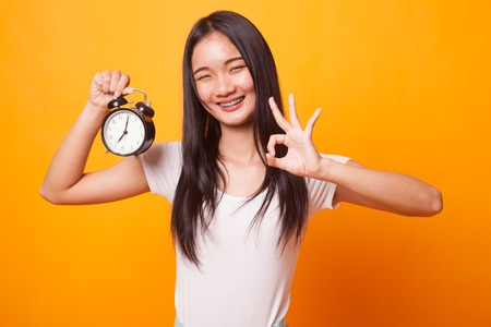 Young Asian woman show OK with a clock on bright yellow background