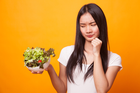 Asian woman hate salad on bright yellow background