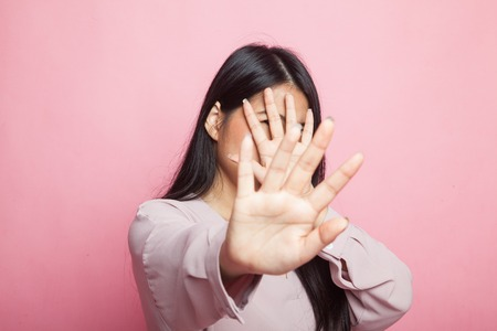 Young Asian woman hide her  face on pink background 版權商用圖片