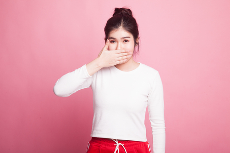 Young Asian woman close her mouth with hand on pink background 写真素材