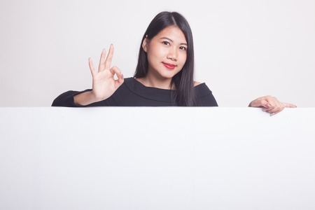 Young Asian woman show OK with blank sign on white background