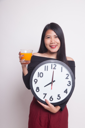 Asian woman with a clock drink orange juice on white background