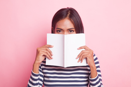 Young Asian woman with a book on pink background