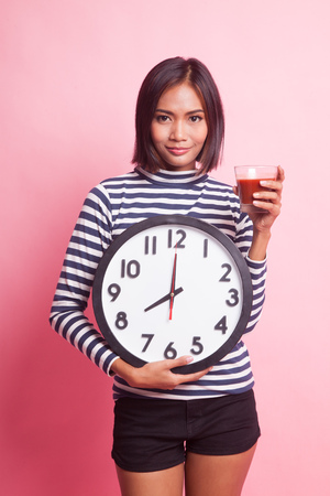 Young Asian woman with tomato juice and clock on pink background