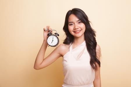 Jeune femme asiatique avec une horloge sur fond beige Banque d'images