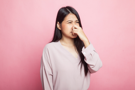 Young Asian woman  holding her nose because of a bad smell on pink background 免版税图像