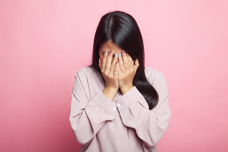 Sad young Asian woman cry with palm to face on pink background Stock Photo