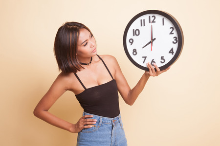Young Asian woman with a clock on beige background