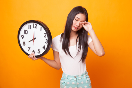 Sleepy young Asian woman with a clock in the morning on bright yellow background