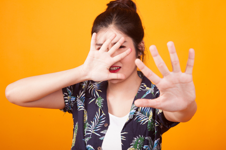 Young Asian woman hide her  face in  tropical shirt on yellow background Imagens