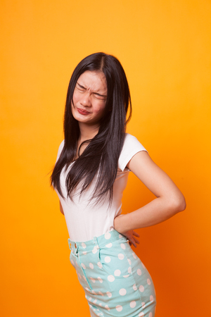 Young Asian woman got back pain on bright yellow background Standard-Bild