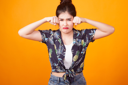 Young Asian woman sad and cry in  tropical shirt on yellow background