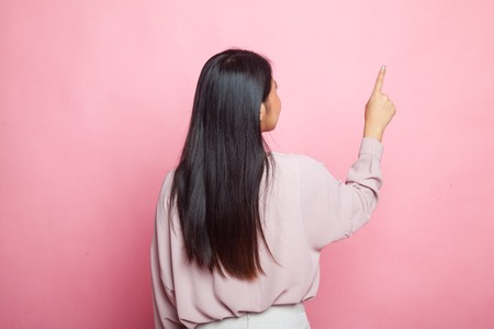Back of Asian woman touching the screen with her finger on pink background