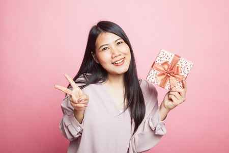 Asian woman show victory sign with a gift box on pink background Stock Photo