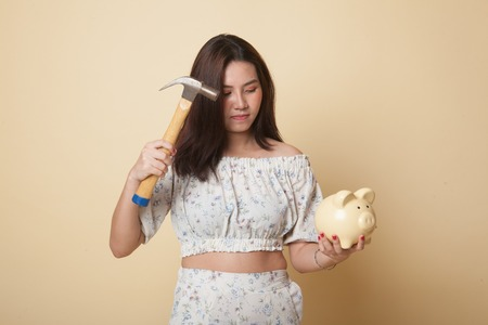 Asian woman with pig coin bank and hammer on beige background