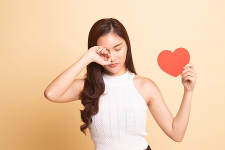 Asian woman sad and cry with red heart   on beige background.