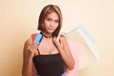 Young Asian woman with shopping bag and blank card on beige background 免版税图像