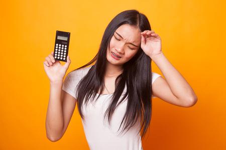 Asian woman got  headache with calculator on bright yellow background Foto de archivo