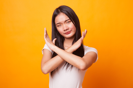 Beautiful young Asian woman say no on bright yellow background 스톡 콘텐츠