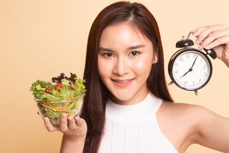 Young Asian woman with clock and salad   on beige background