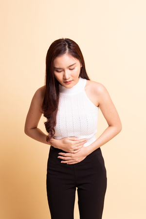 Young Asian woman got stomachache   on beige background