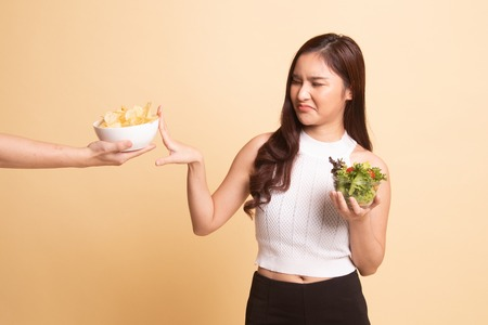Young Asian woman with salad say no to potato chips   on beige background Stock Photo