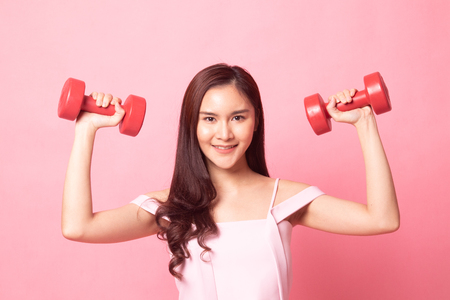 Young Asian woman with red dumbbell on pink background