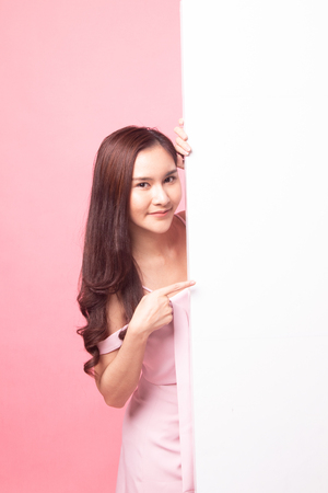 Young Asian woman point to a  blank sign on pink background 免版税图像