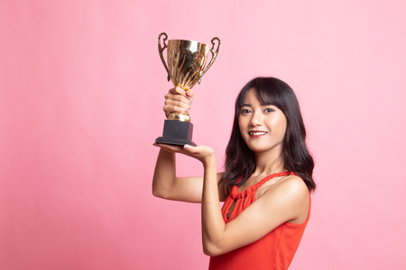 Successful young asian woman holding a trophy on pink background