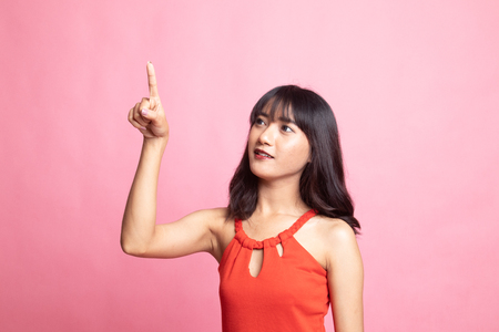 Asian woman touching the screen with her finger on pink background