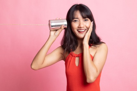 Happy Young Asian woman listen with tin can phone on pink background