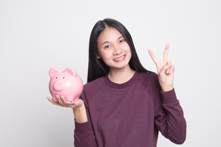 Asian woman show victory sign with pig coin bank on white background Stock Photo