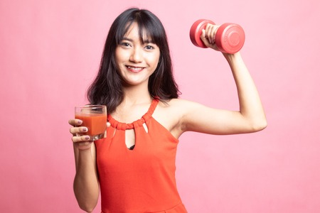 Young healthy Asian woman with dumbbell and  tomato juice on pink background