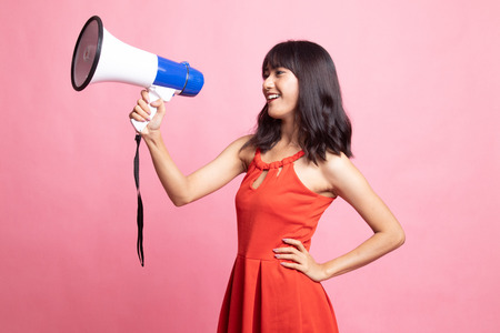 Beautiful young Asian woman announce with megaphone on pink background