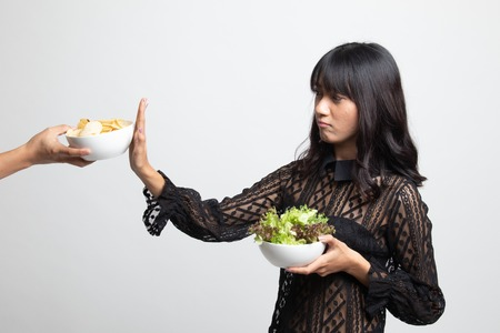 Young Asian woman with salad say no to potato chips on white background Stock Photo