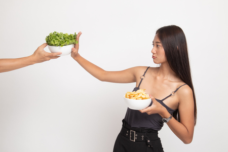 Young Asian woman with potato chips say no to salad on white background