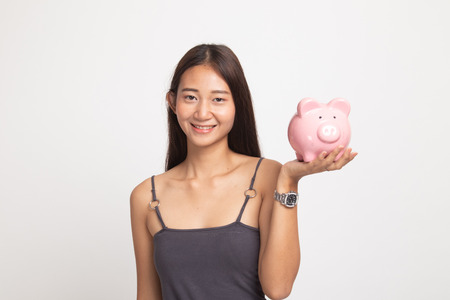 Young Asian woman with a pig coin bank on white background Фото со стока