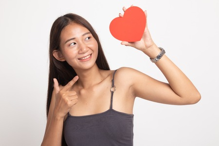 Asiatische Frau zeigen auf rotes Herz auf weißem Hintergrund