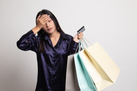Unhappy young Asian woman with shopping bags and credit card on white background