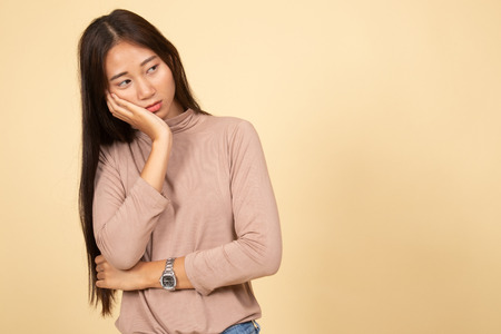 Beautiful young Asian woman get bored  on beige background