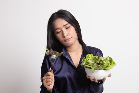 Asian woman hate salad on white background