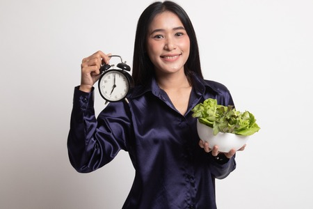 Young Asian woman with clock and salad on white background