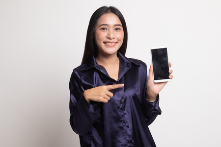 Young Asian woman point to mobile phone on white background