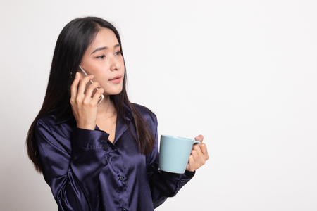 Young Asian woman with mobile phone and coffee cup on white background